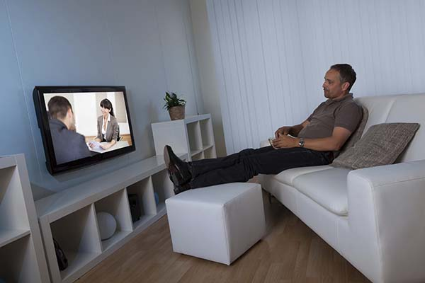 Man sits on couch and watches television.