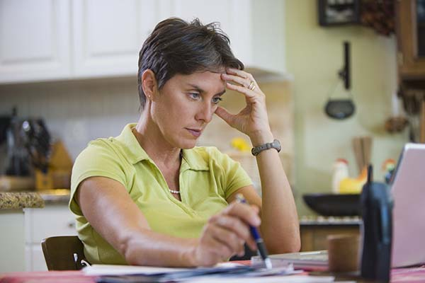 Woman sits with laptop and papers at kitchen table.