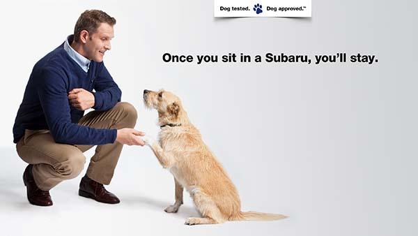 Ad for Subaru vehicles. Man kneeling while sitting dog shakes his hand.