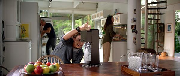 Teenager having fun while using SodaStream.